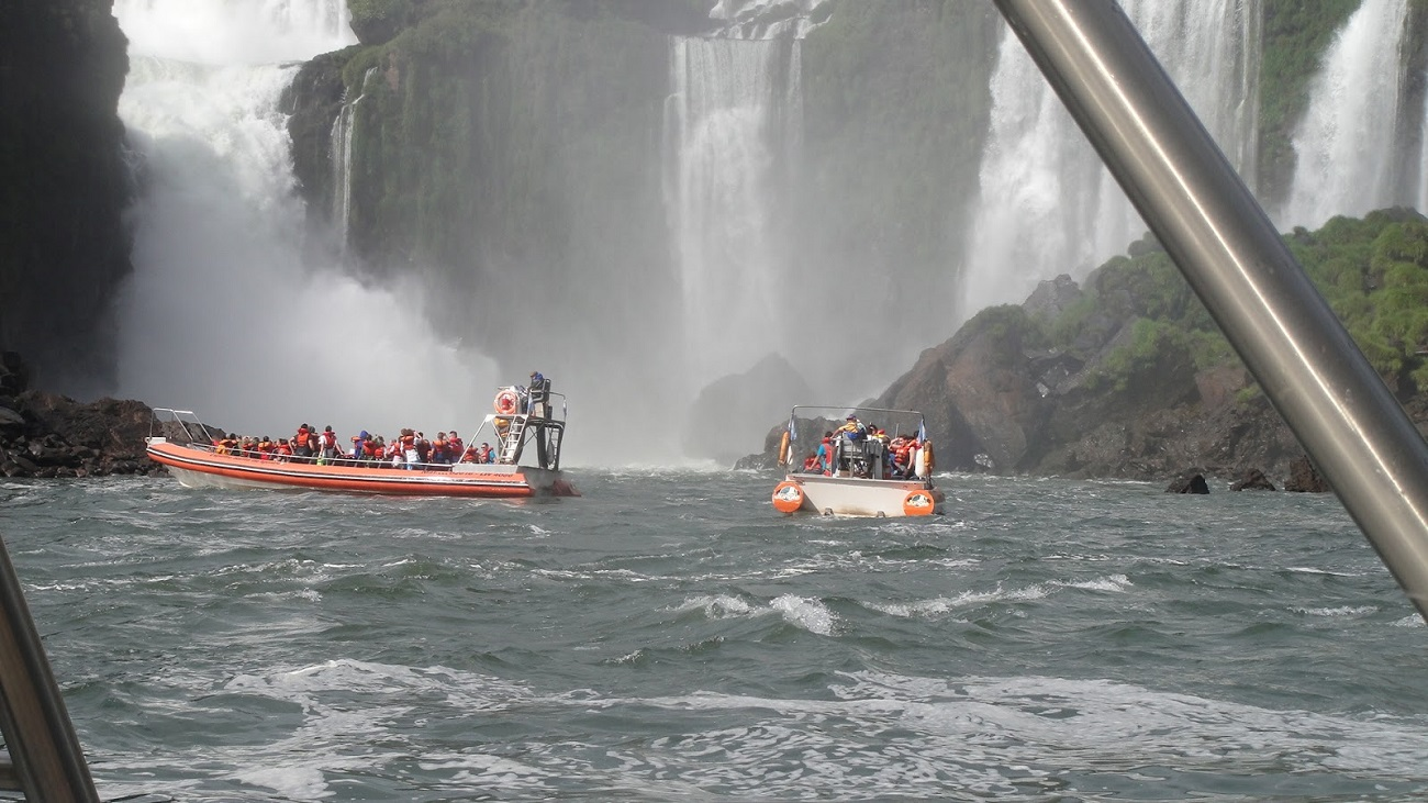 Cascada Iguacu şi turişti aflaţi în excursii pe apele învolburate