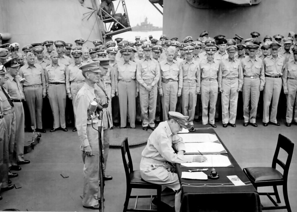 Douglas MacArthur semnând actele predării japoneze pe puntea USS Missouri