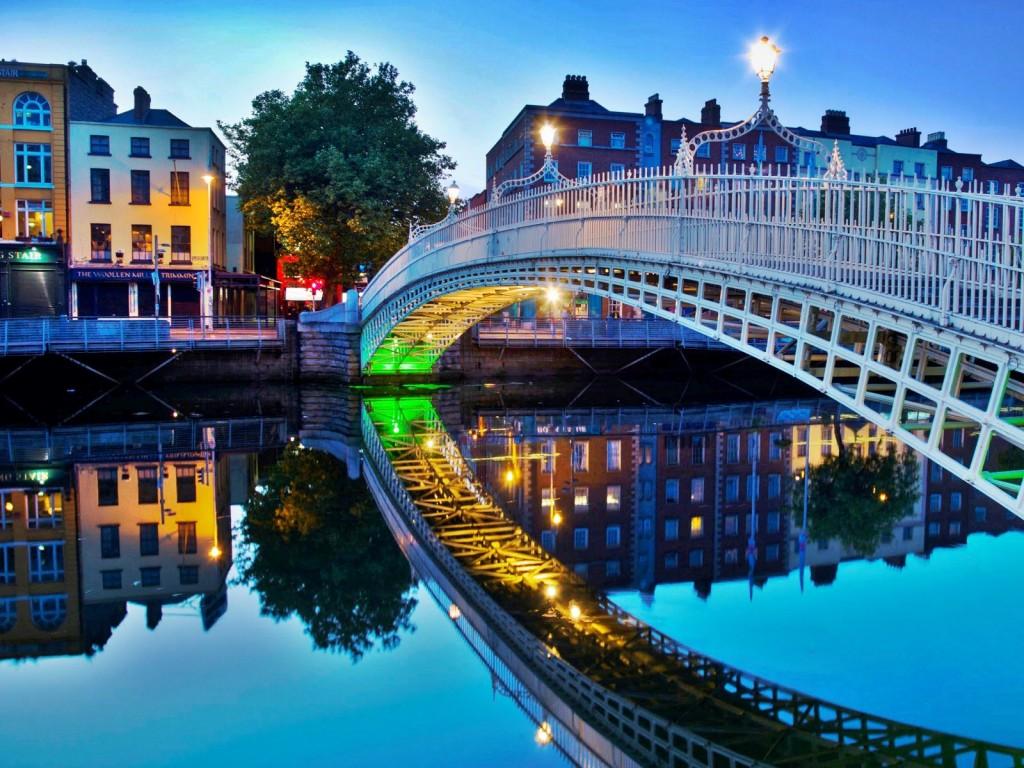 Luminile orașului reflectate de un luciu perfect de apă în Dublin