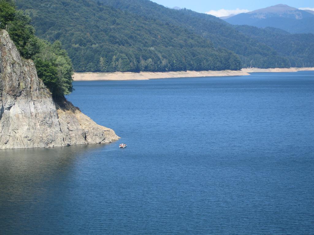 Omul si barca, atat de mici pe Lacul Vidraru