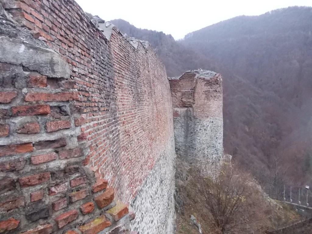 Zidul gros din caramizi are la baza un alt zid din pietre de rau