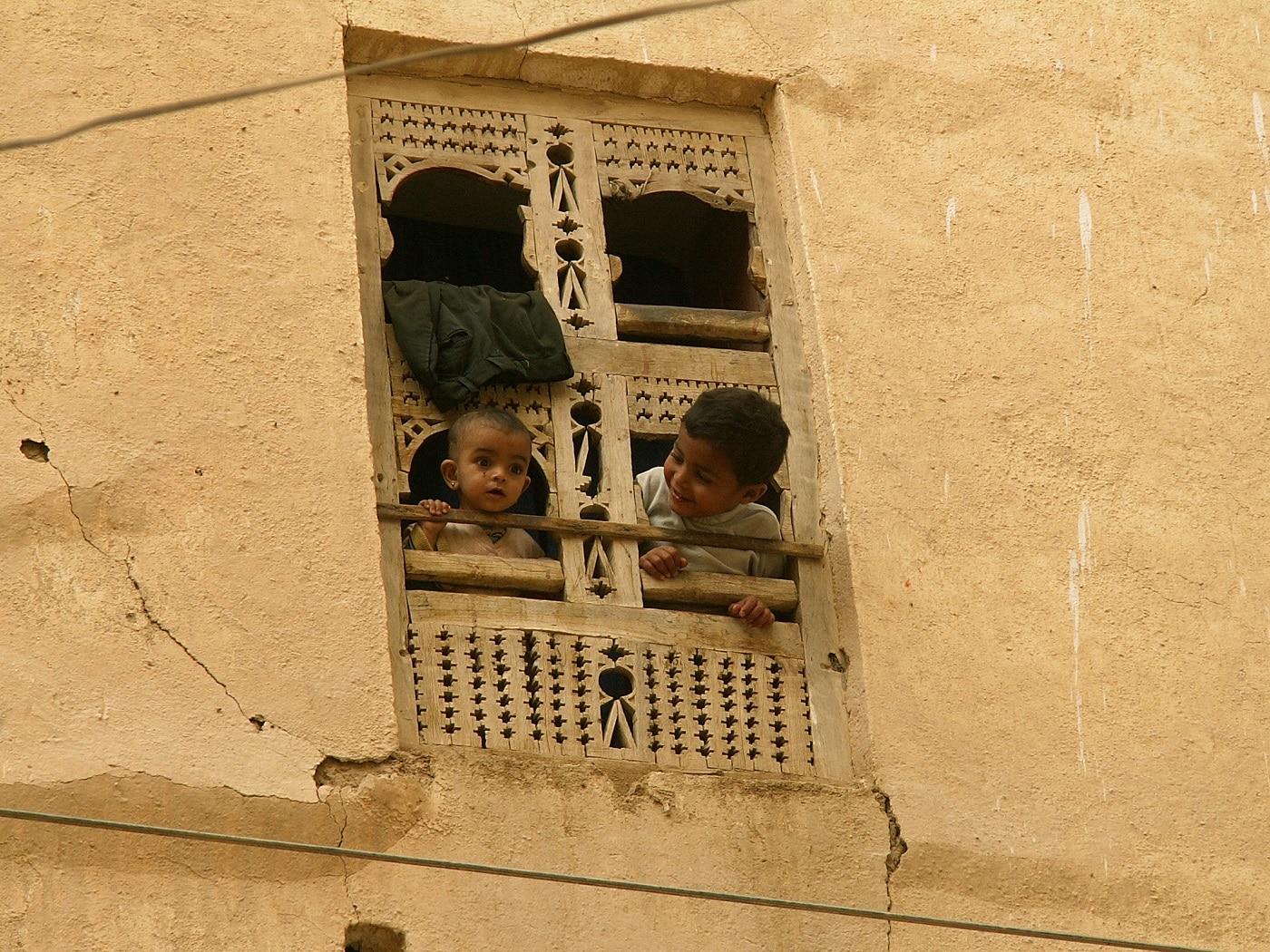 Doi copii veseli stau la geamurile construcțiilor din noroi